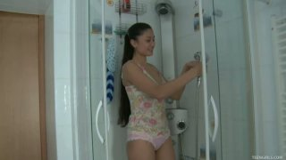 Passionate teen chick Ming strokes her wet body in a shower and fingers her pussy