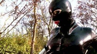 Alluring super hero in latex costume poses on cam